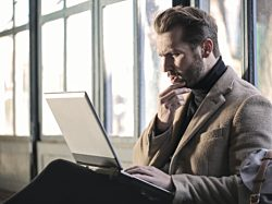 Man looking at laptop, looking confused and scratching his beard